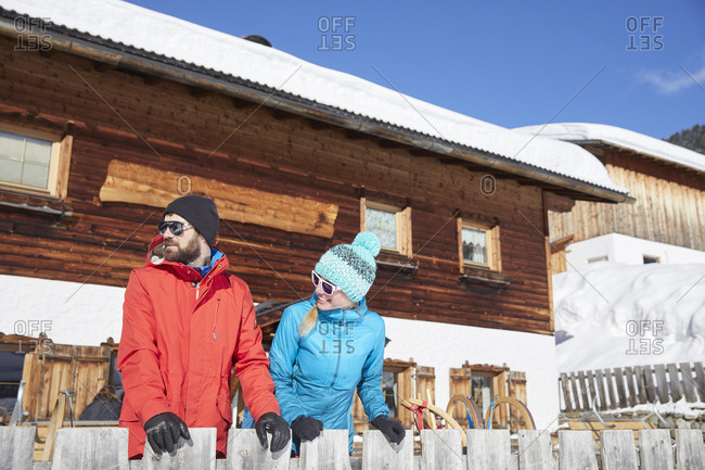 Couple in winter at wooden mountain hut looking around