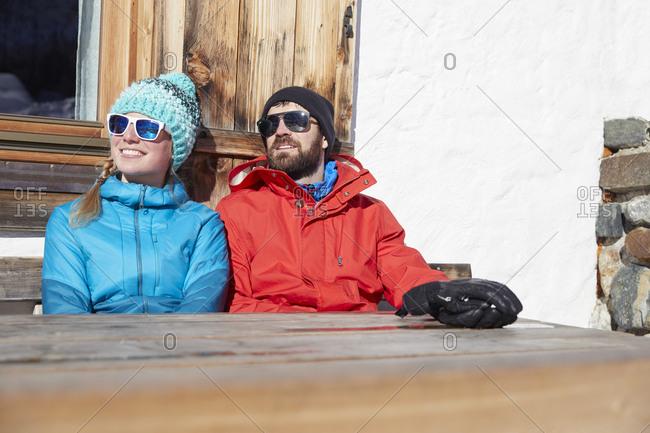 Couple sunbathing in winter at wooden mountain hut