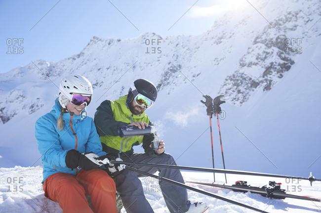 Austria- Tyrol- Kuehtai- two skiers in winter landscape having a break