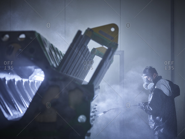 Worker cleaning engine block in washing bay