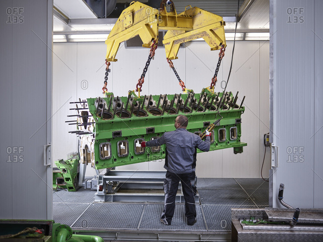 Worker in factory lifting engine block with crane