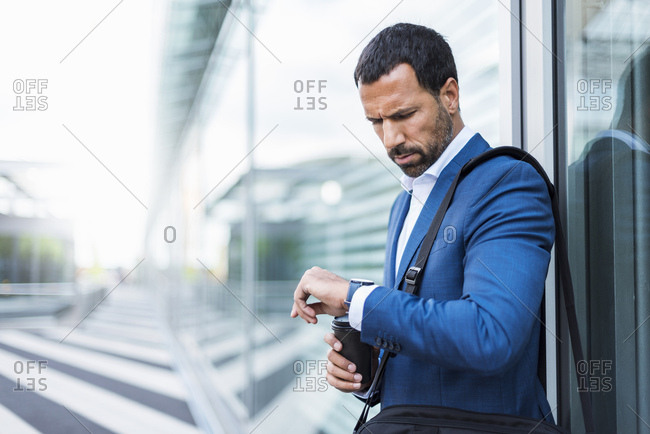 Businessman with cup of coffee- looking on his watch