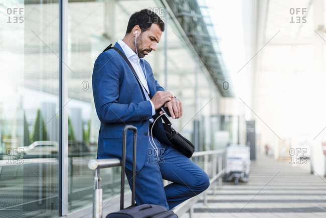 Businessman at airport- looking on watch