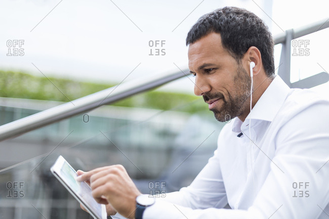 Businessman using tablet- earphones