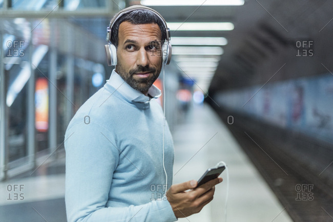 Businessman using smartphone at metro station