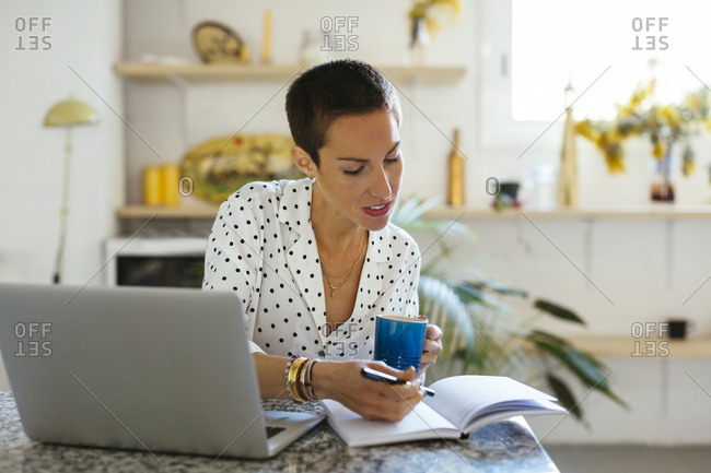 Woman drinking coffee and using laptop and notebook on table