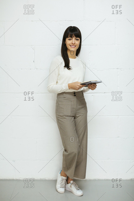 Portrait of smiling young woman with notebook standing at brick wall