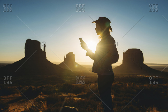 USA- Utah- Woman using mobile at sunrise in Monument Valley
