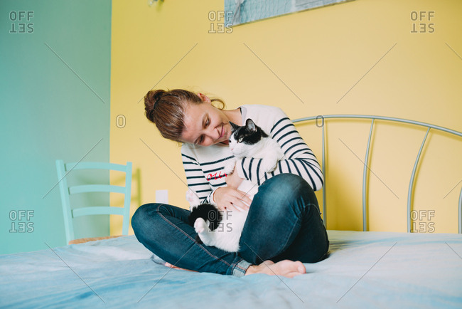 Happy woman with a black and white cat on the bed