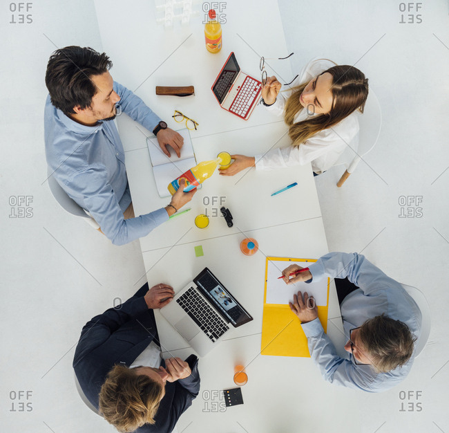 Four business people at meeting table in office- top view