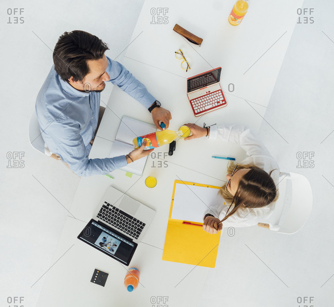 Two business people at meeting table in office- top view