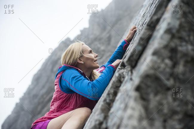 Austria- Salzburg State- Filzmoos- Female hiker climbing on rock