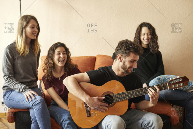 Happy friends listening to man playing guitar on couch