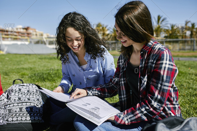 Two smiling female students sitting in park learning together
