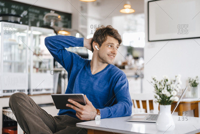 Smiling man in a cafe with earphone- laptop and tablet