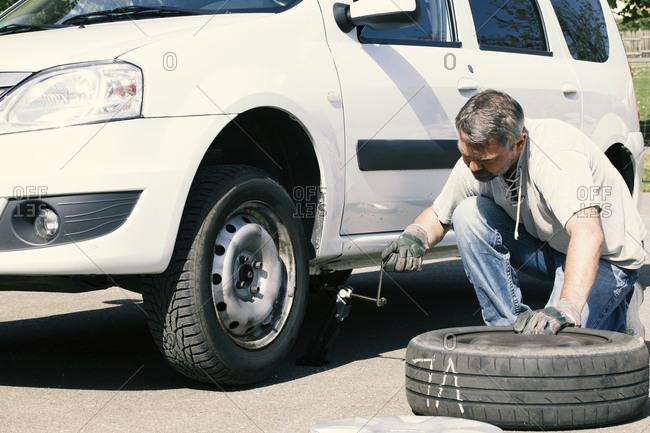 Mature man changing car tires- top view