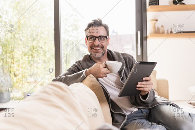 Portrait of smiling man with cup of coffee sitting on couch with tablet