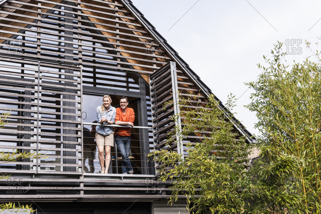 Smiling mature couple standing on balcony of their house