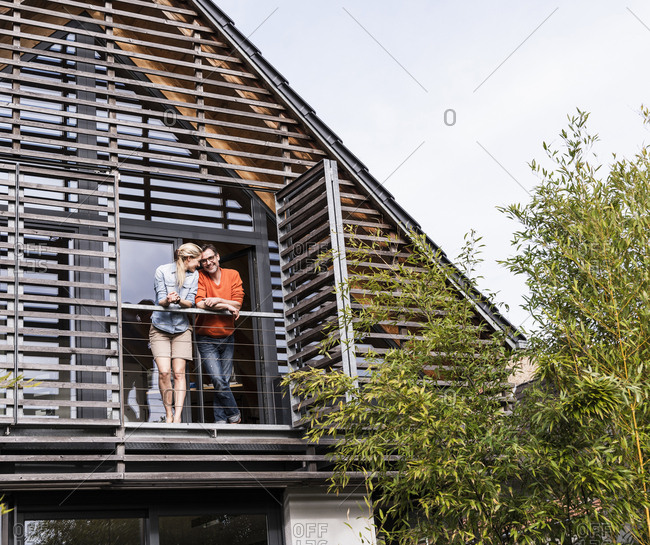 Happy mature couple standing on balcony of their house