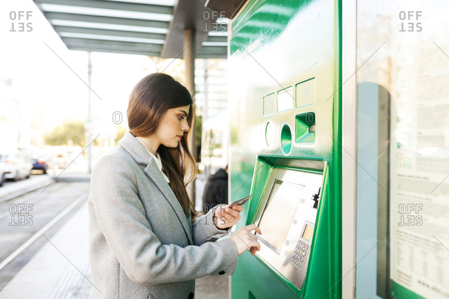 Spain- Barcelona- woman buying ticket from automated machine at station