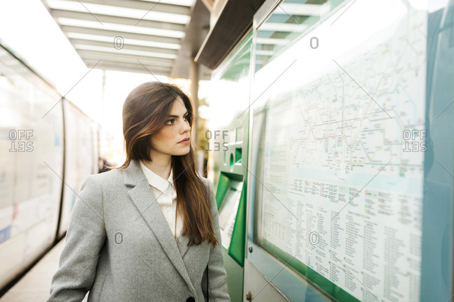 Spain- Barcelona- portrait of young businesswoman looking at map at station