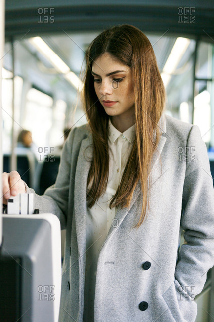 Portrait of young woman validating ticket in tramway