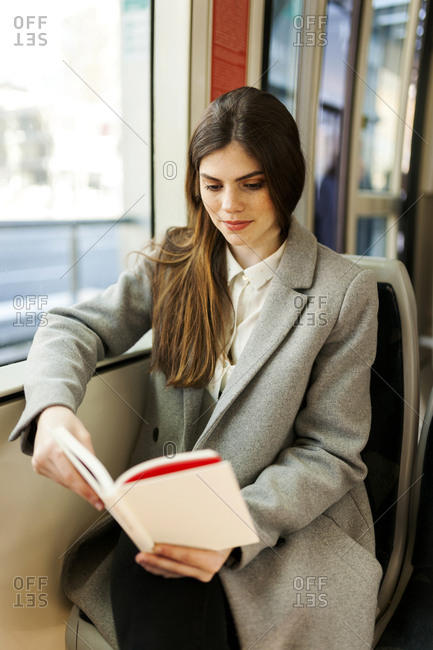 Portrait of young woman reading book in tramway