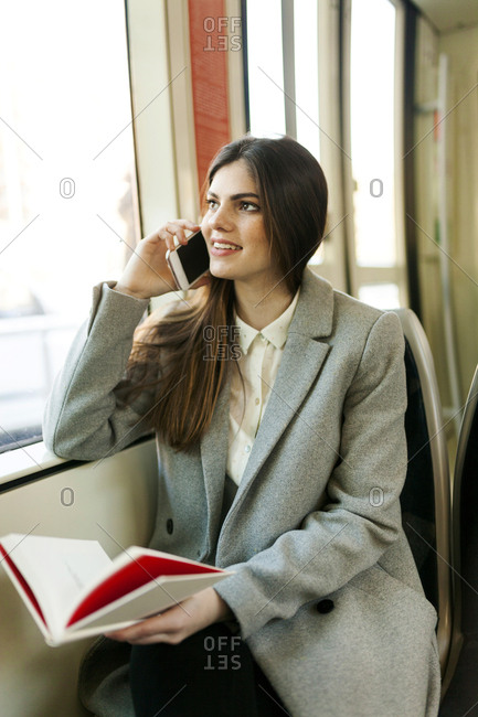 Portrait of smiling young woman on the phone in tramway