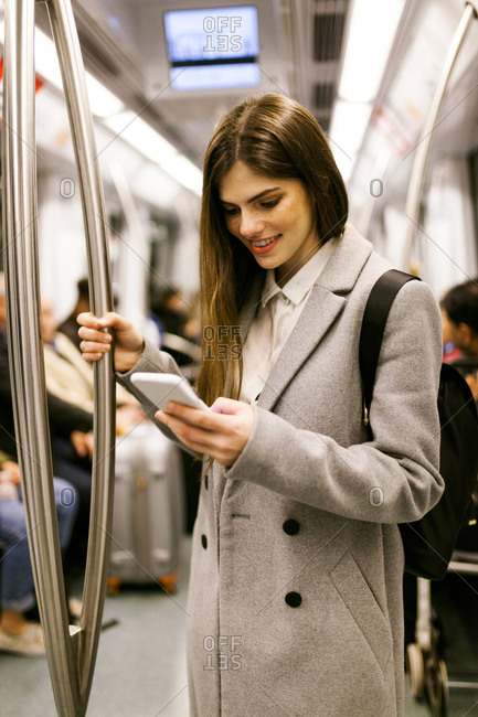 Spain- Barcelona- young businesswoman using cell phone in underground train
