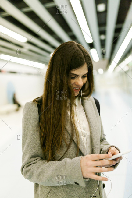 Smiling young woman using cell phone and earphones