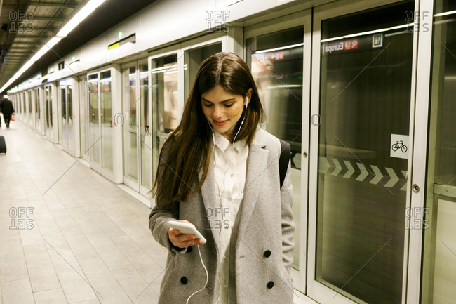 Young woman using cell phone and earphones in a passageway