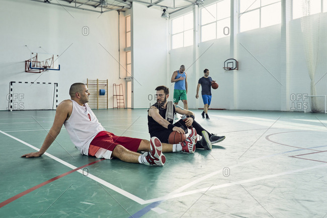 Basketball players during break- sitting on court