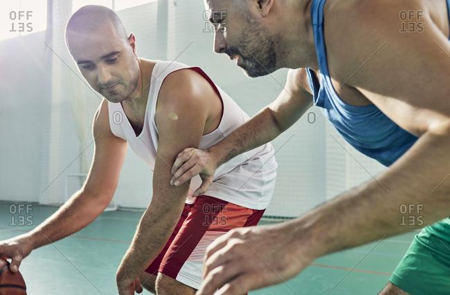 Men playing basketball- defense