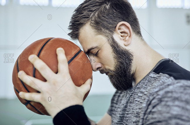 Man with basketball- closed eyes- indoor