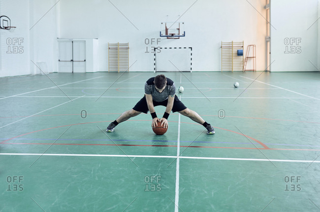 Man with basketball- stretching legs- indoor
