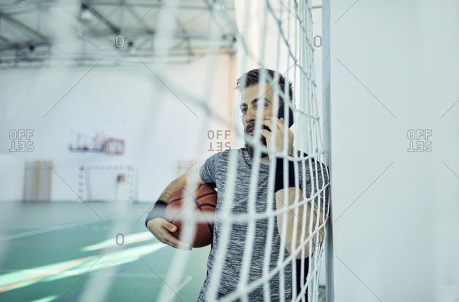 Man with basketball using smartphone behind net- indoor
