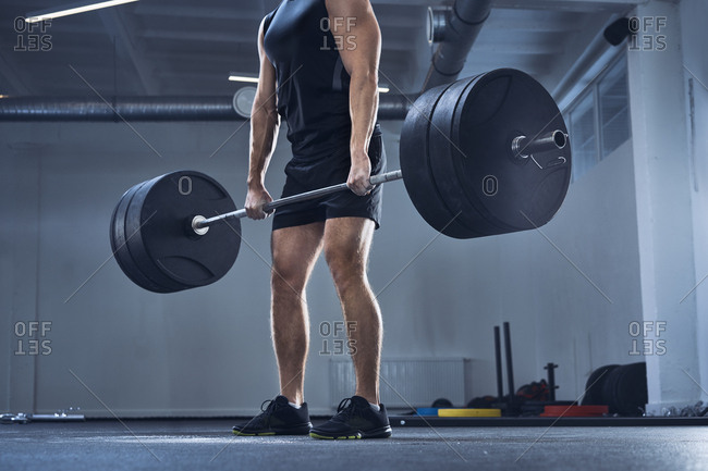 Athletic man doing deadlift exercise at gym