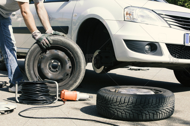 Man changing car tires- partial view