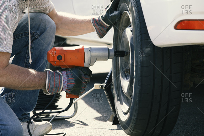 Man changing car tire- partial view