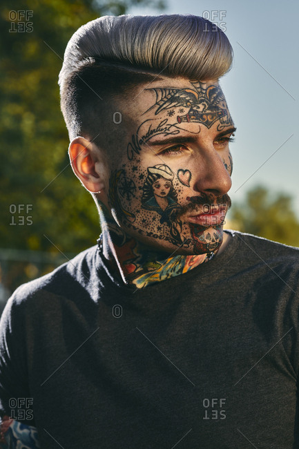 Portrait of tattooed young man outdoors