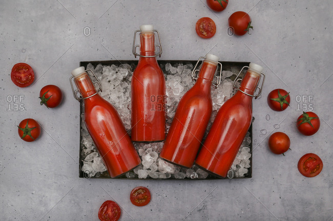 Ice-cooled homemade tomato juice in swing top bottles