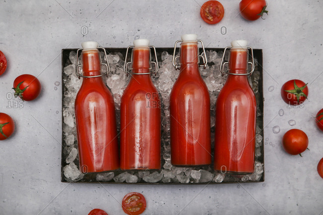 Row of four ice-cooled swing top bottles with homemade tomato juice
