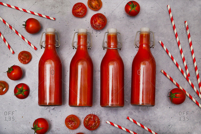 Row of four swing top bottle of homemade tomato juice- straws and tomatoes on grey ground