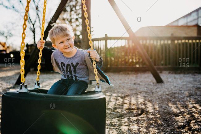 Little boy swinging on tire swing