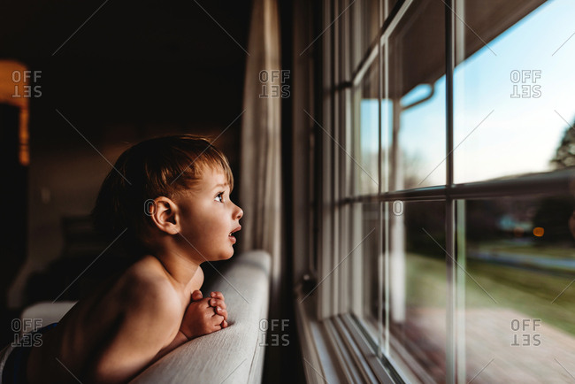 Little boy looking out window at sunset