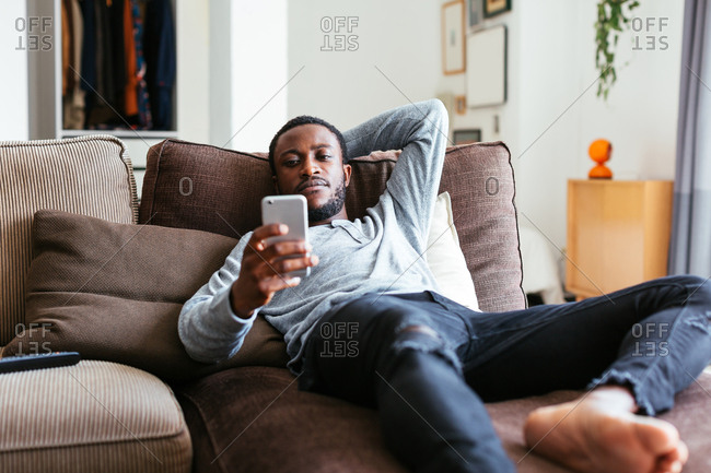 Man chatting on phone relaxing on sofa