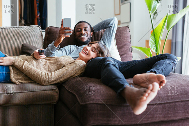 Smiling young couple watching a tv movie relaxing on sofa
