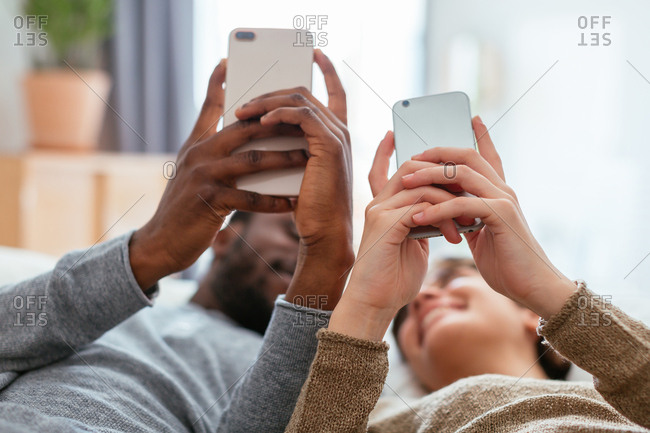 Young couple using their phones lying on bed