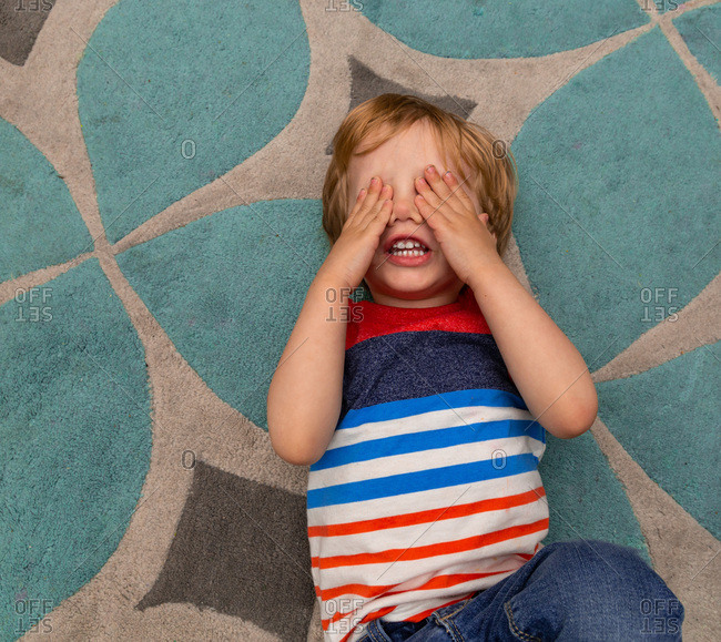 Toddler boy lying on the floor of his bedroom and covering his eyes