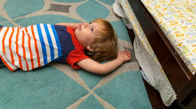 Toddler boy lying on the floor of his bedroom and looking up